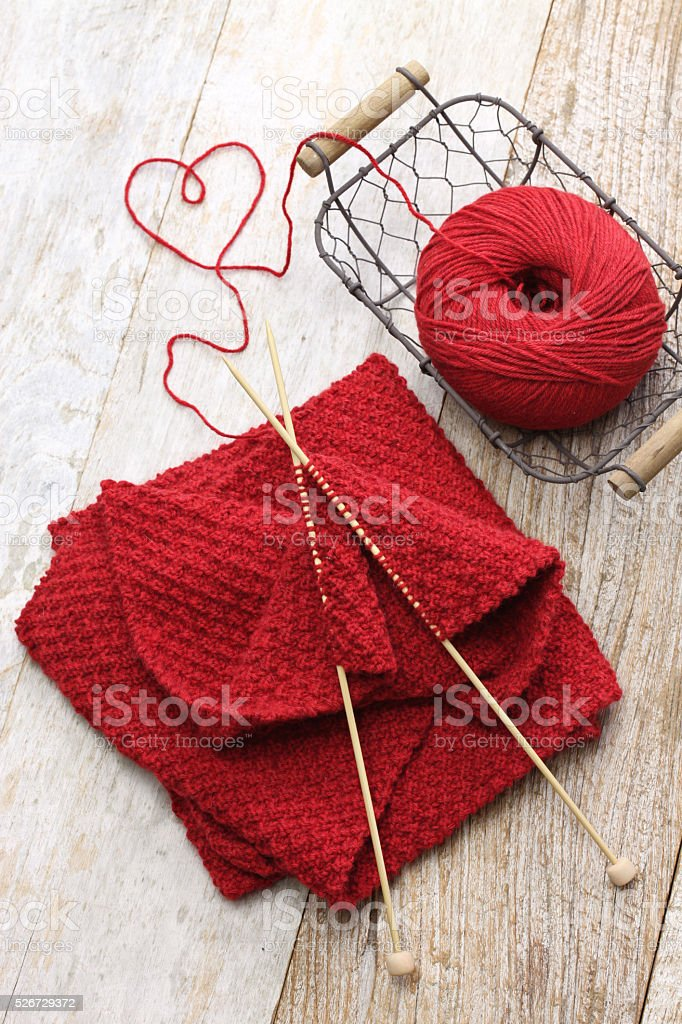 hand knitted red scarf and heart shaped thread stock photo