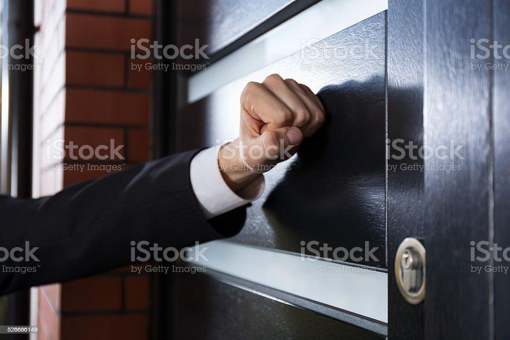 Hand knocking on the door stock photo