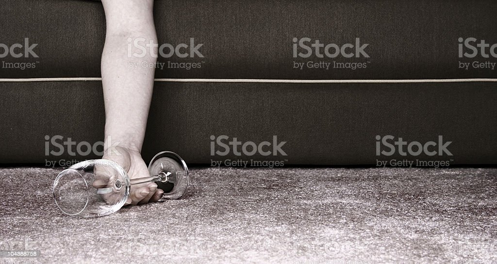 Hand laying on the floor with glass of wine nearby royalty-free stock photo