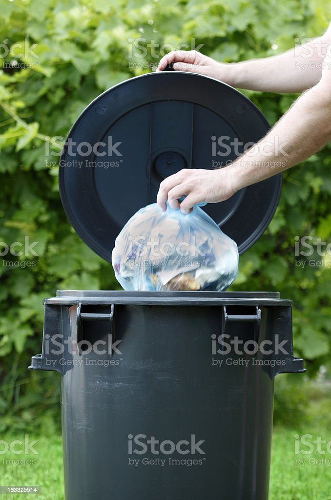 Hand lifting a garbage bin lid, another hand disposes trash stock photo