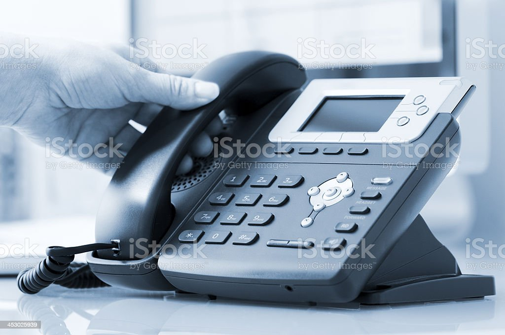 Hand lifts receiver from modern office telephone royalty-free stock photo