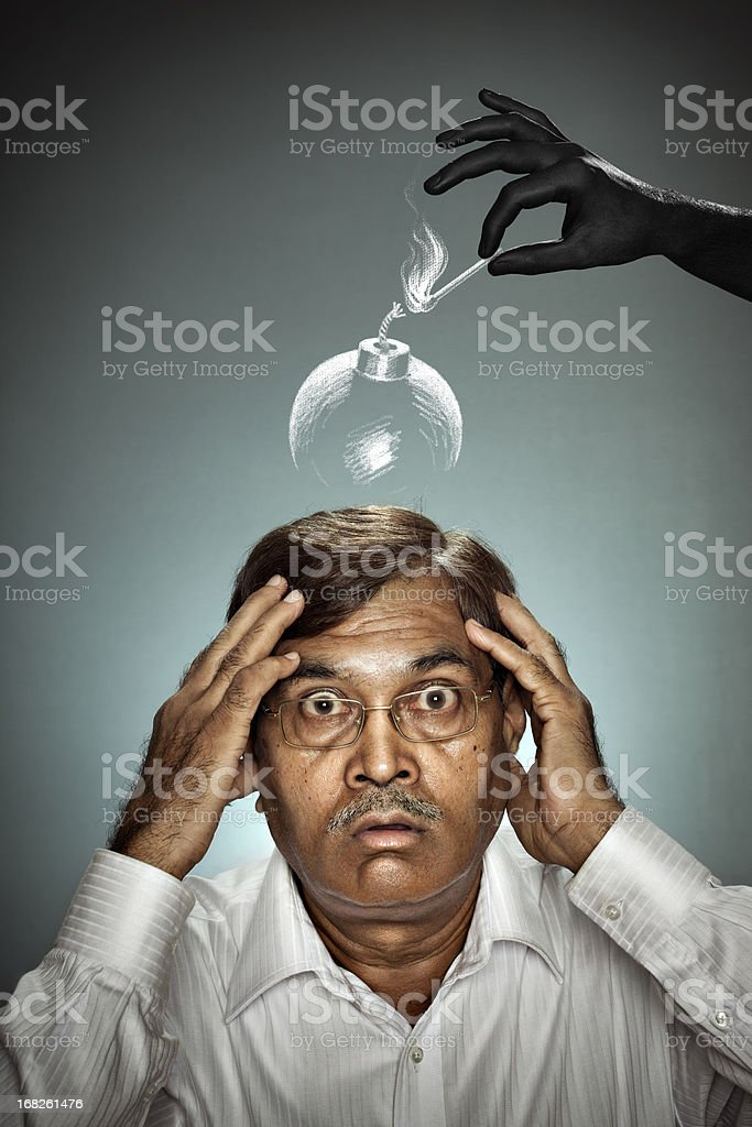 Hand lighting bomb above the head of shocked mature man. royalty-free stock photo