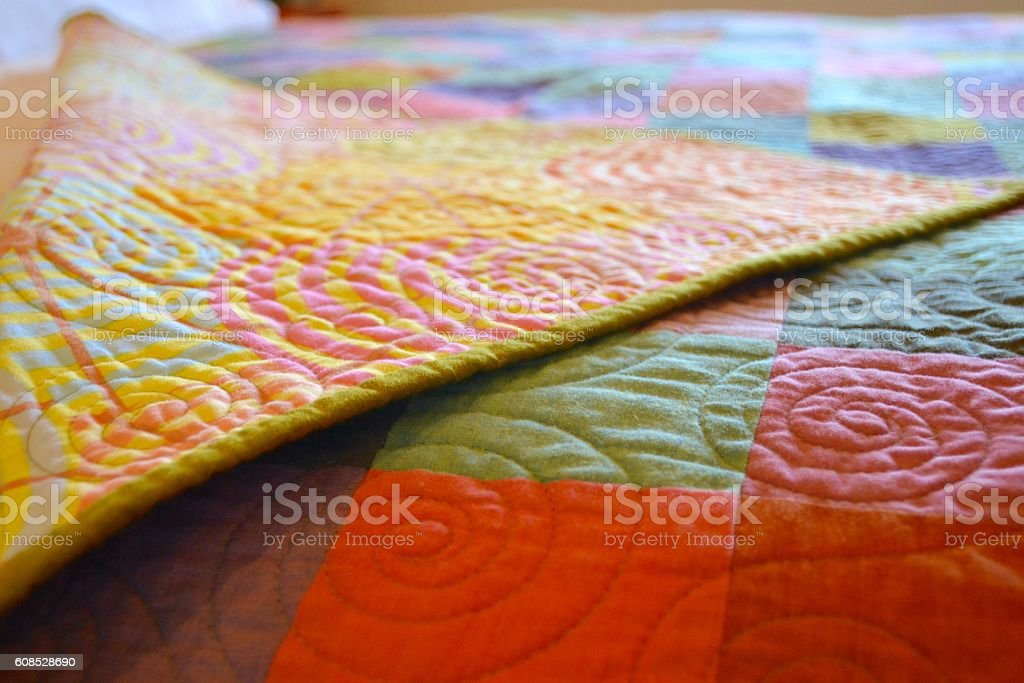 Hand made craft quilt folded back stock photo