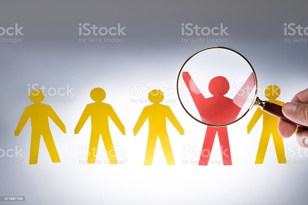 Hand Magnifying Red Paperman Representing Recruitment stock photo