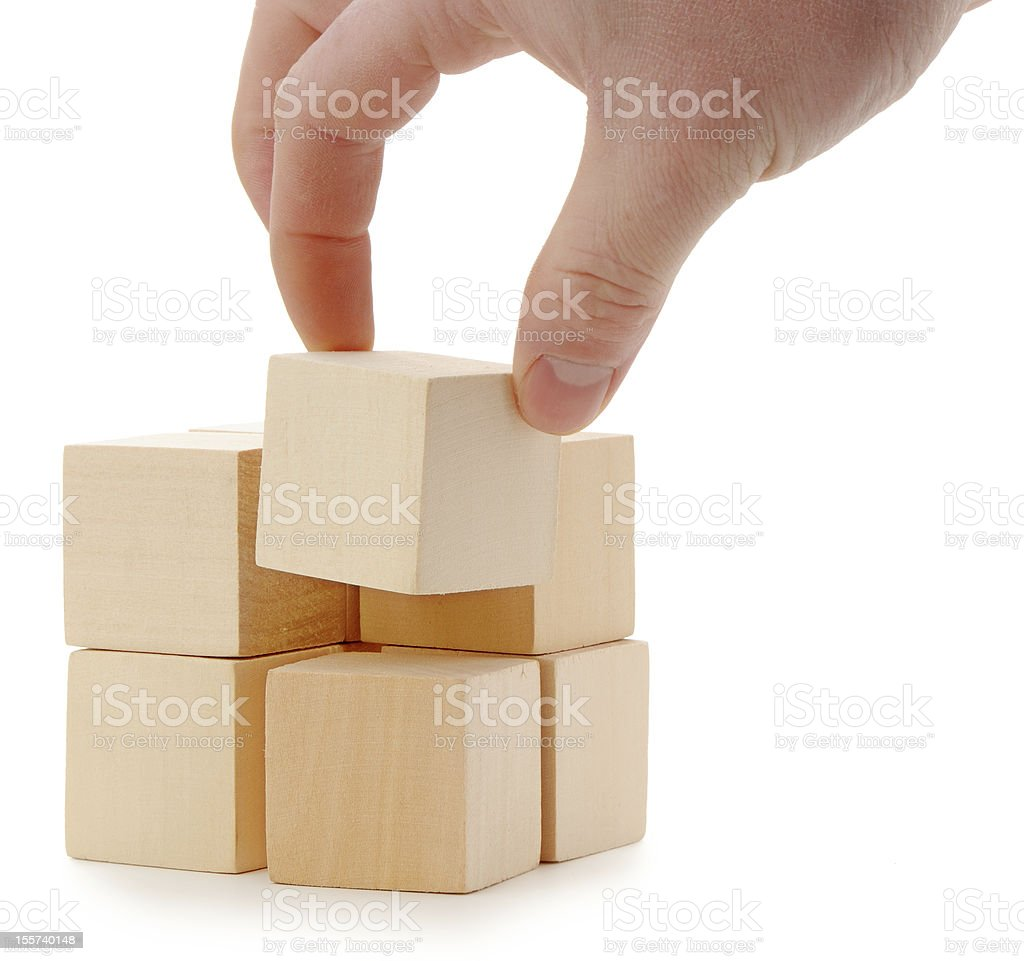 A hand making a large wooden cube with smaller cubes royalty-free stock photo