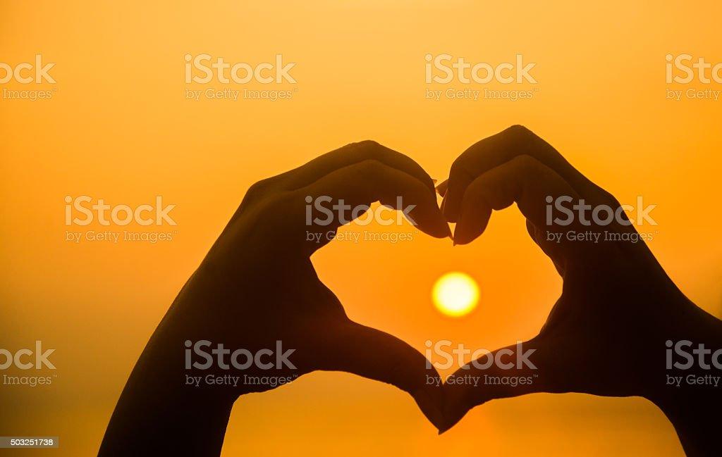 hand making heart shape over sunset stock photo
