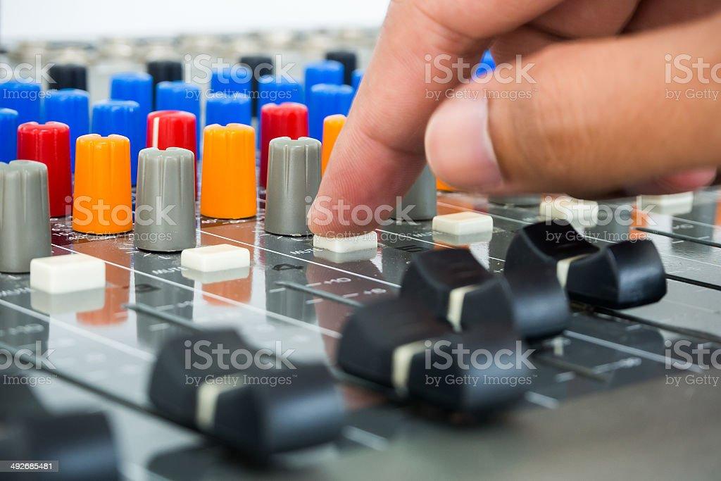 Hand making push button on an audio soundboard stock photo