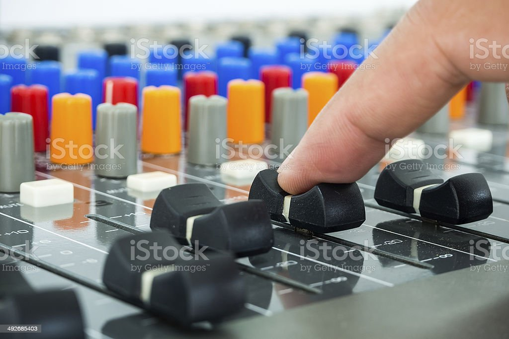 Hand making slide on an audio soundboard stock photo