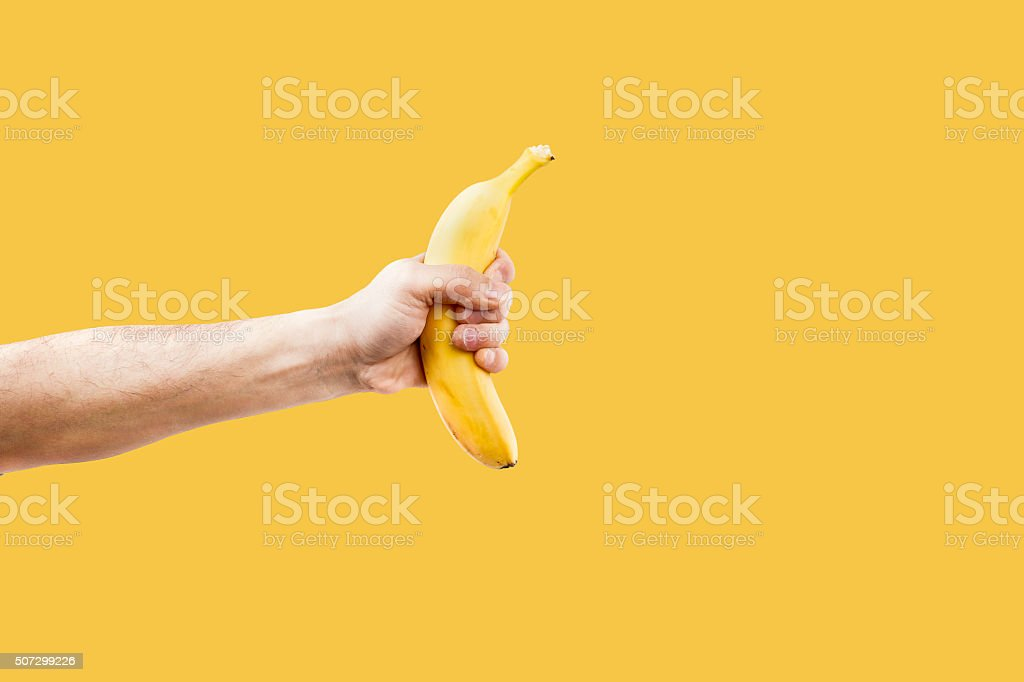 Hand male holding a shape banana telephone. stock photo