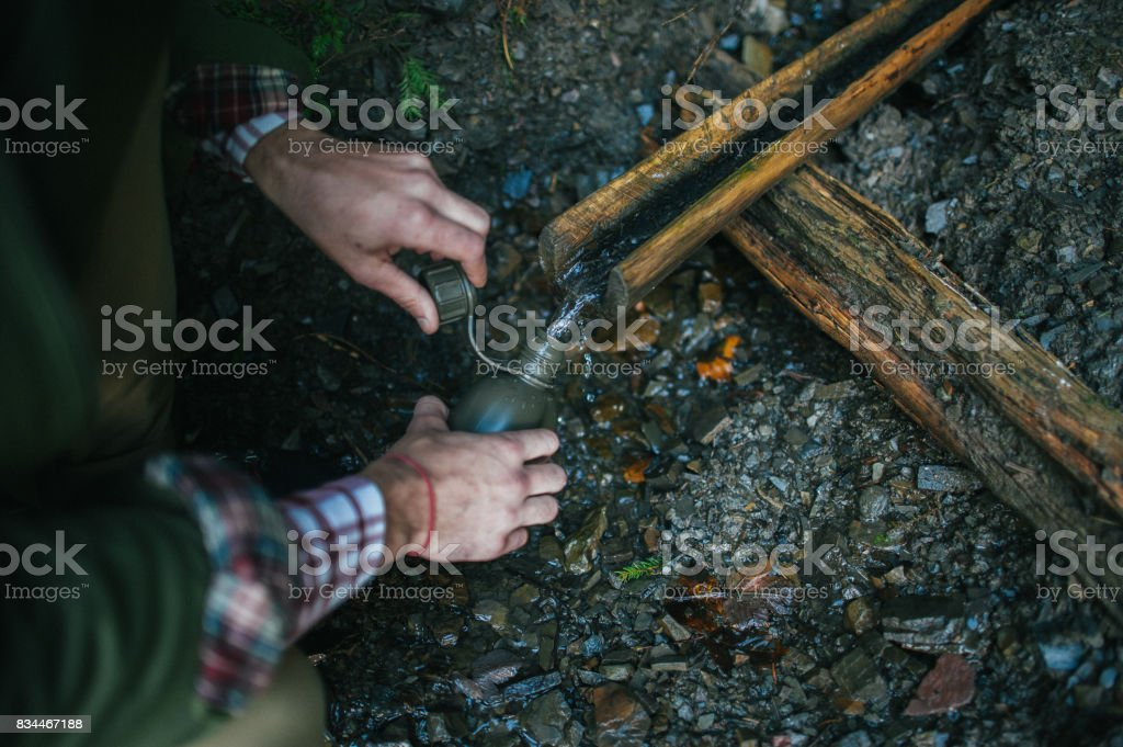 hand Man filling up his Military canteen with water from the riv stock photo