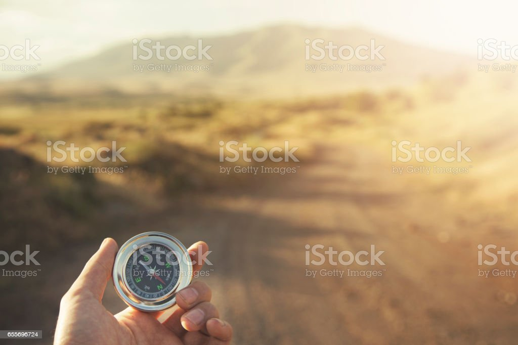 Hand man holding compass navigator on road way stock photo