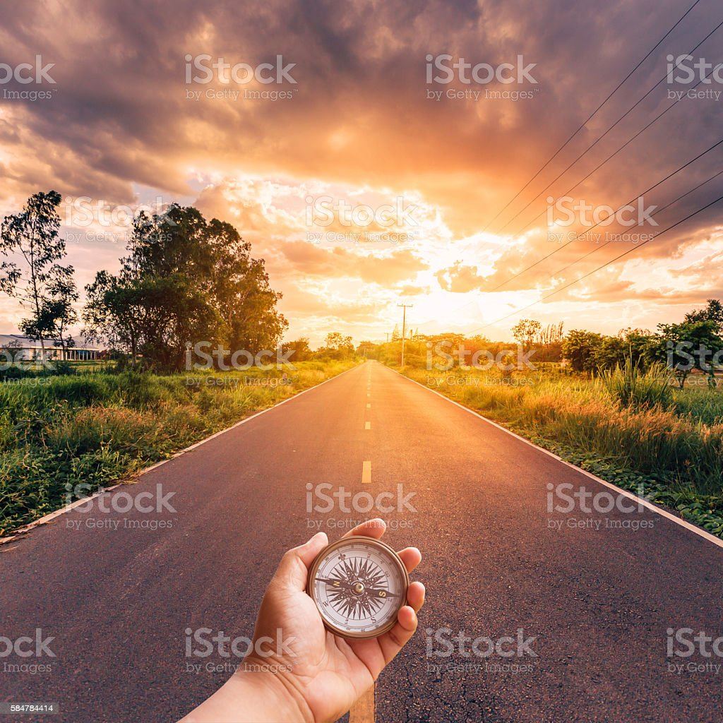 Hand man holding compass on road with sky sunset. stock photo