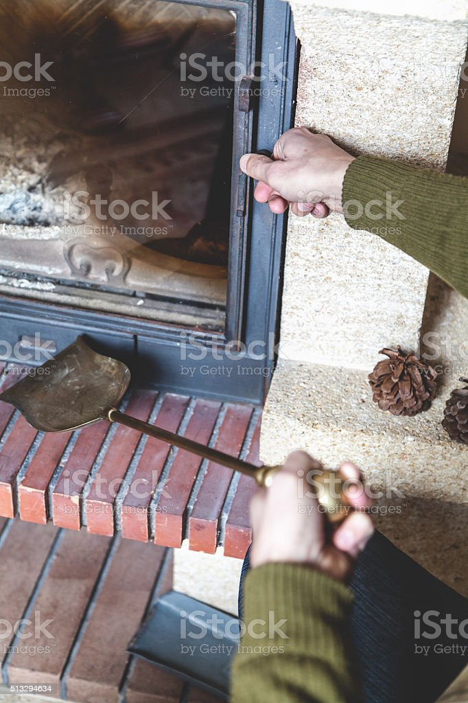Hand man opens door of fireplace stock photo