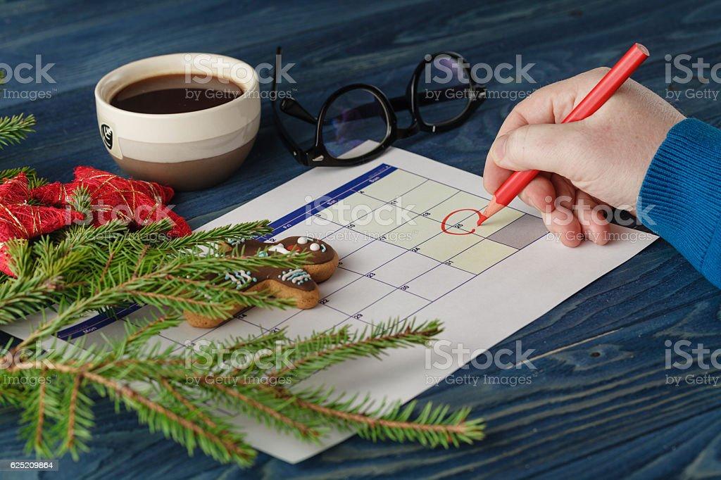 Hand  mark Christmas date on a calendar stock photo