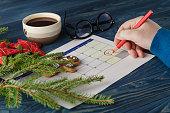Hand  mark Christmas date on a calendar