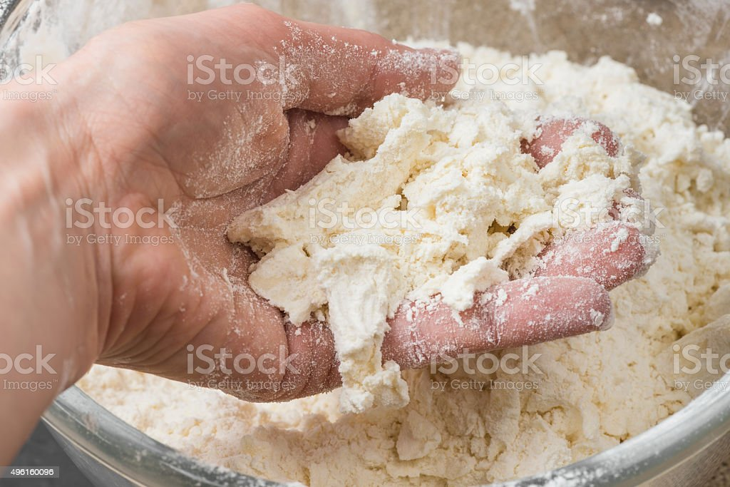 hand mixing the flour and butter in glass bowl stock photo