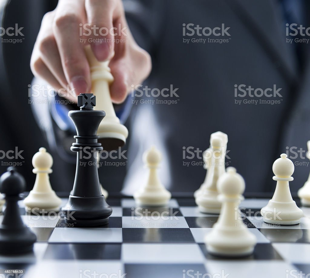 Hand moving a king chess piece over a chess board stock photo