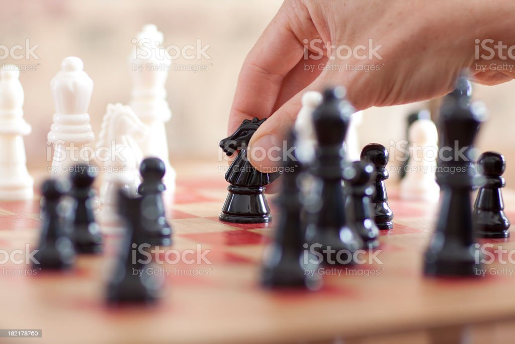 Hand moving a Knight piece on a chessboard stock photo