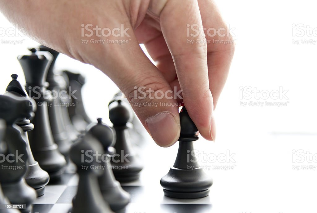 A hand moving the first black chess piece up one space  stock photo
