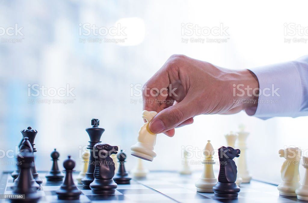 Hand moving the horse in chess game stock photo