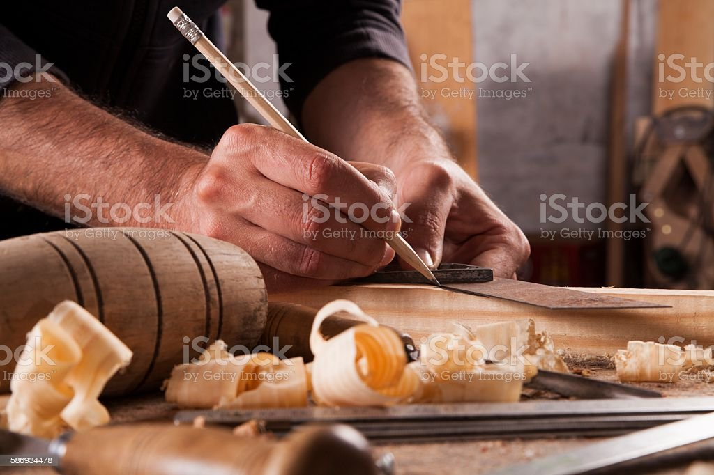 hand of a carpenter taking measurement of a wooden plank stock photo
