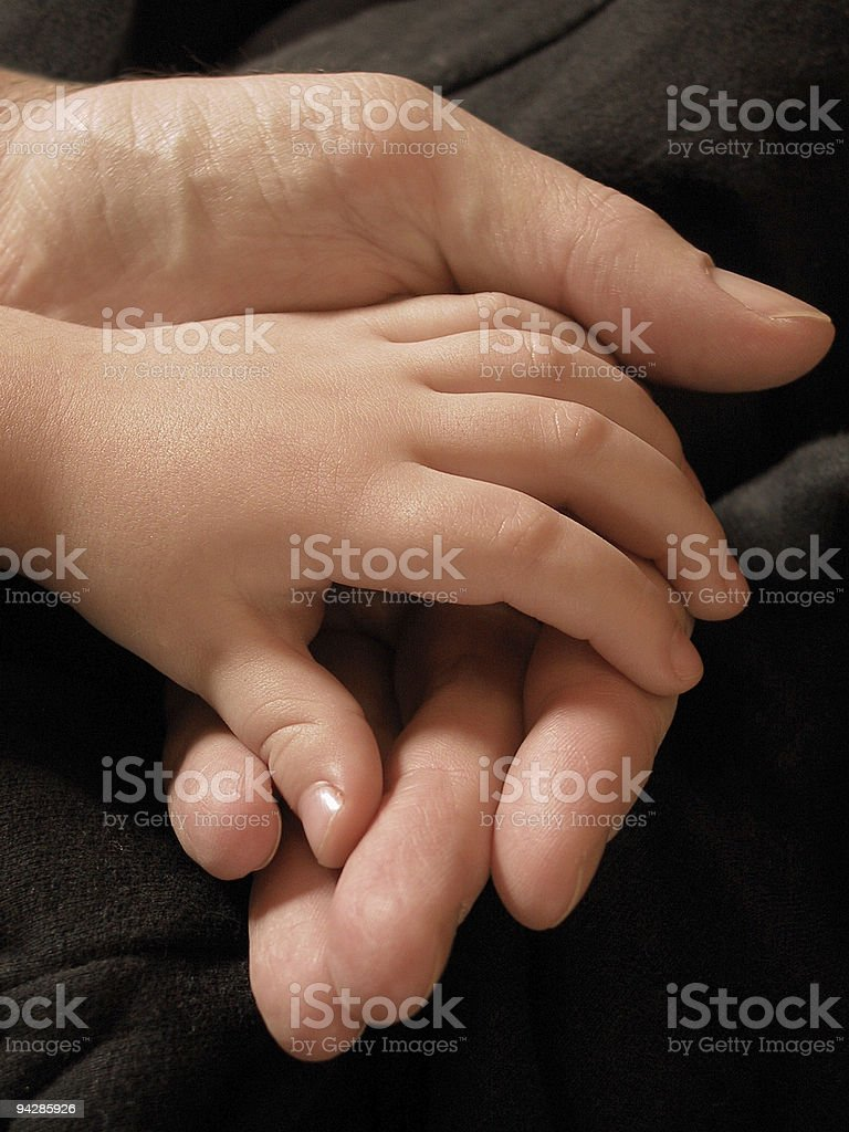 Hand of a child and his father stock photo