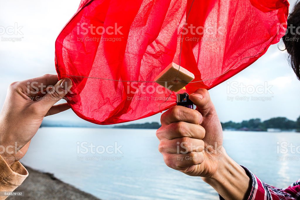 Hand of a couple igniting Chinese lampion with a lighter. stock photo