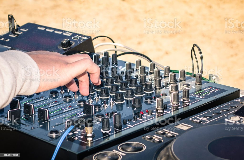 Hand of a deejay playing music on professional mixing controller stock photo