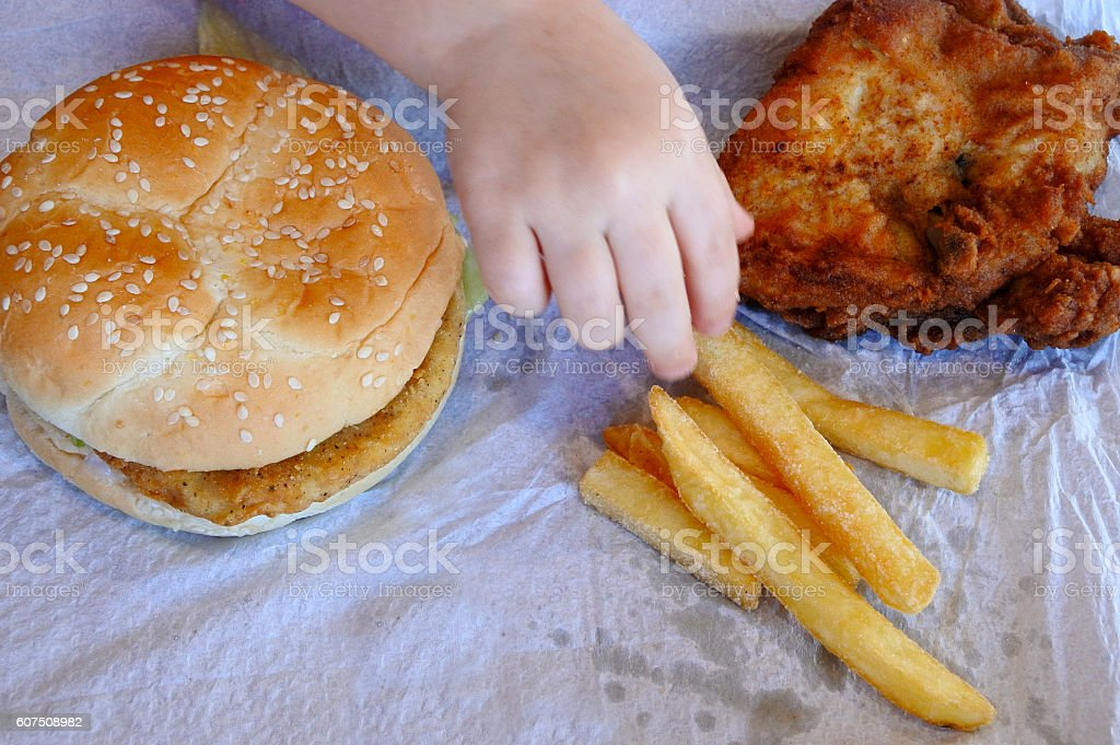 Hand of a little girl ready to eat fast food stock photo