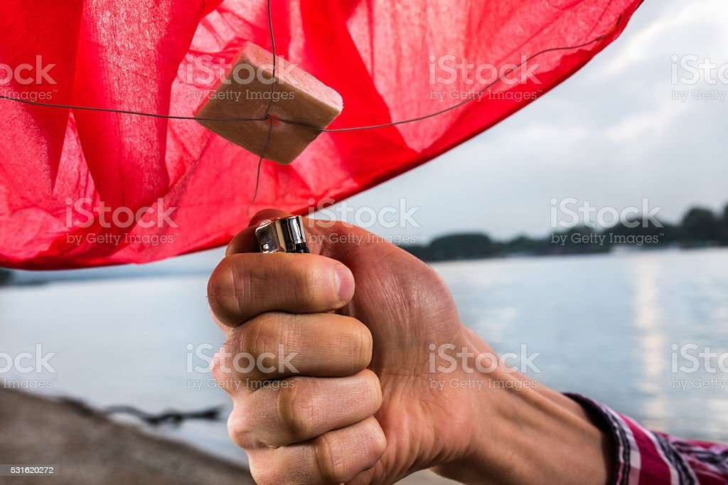 Hand of a man igniting Chinese lampion with a lighter. stock photo