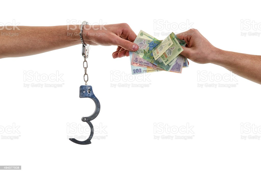 Hand of a man in handcuffs giving bribe stock photo