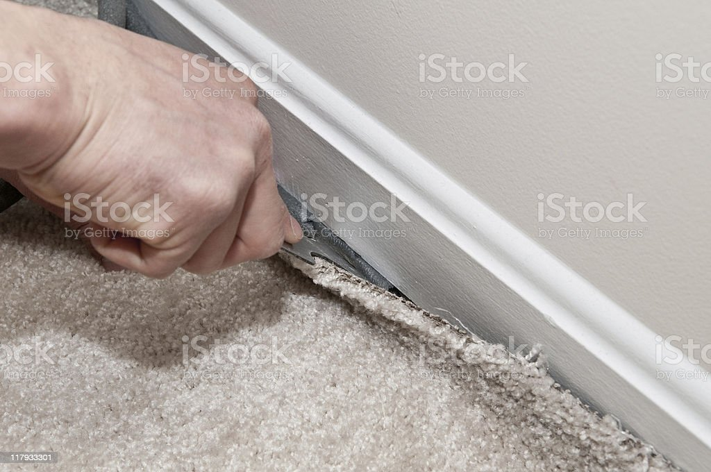 Hand of a man laying a carpet against a skirting board stock photo
