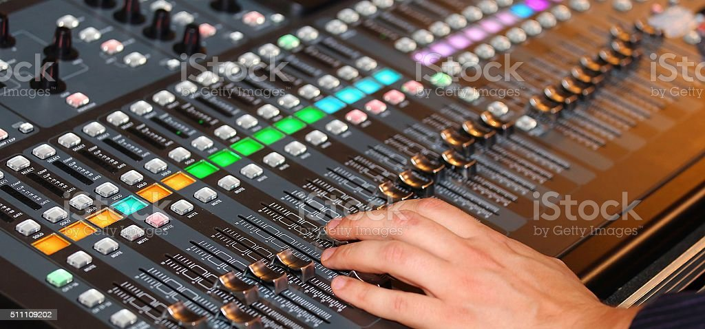 Hand of a man with potentiometers and sound equalizer stock photo