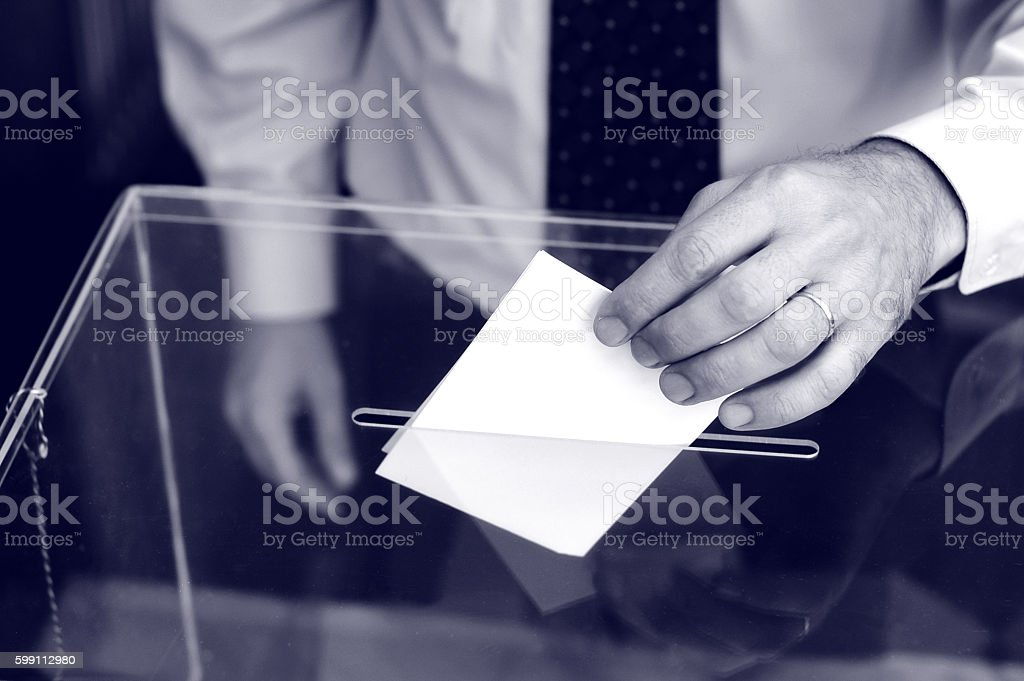 Hand of a person putting a ballot into voting box. stock photo