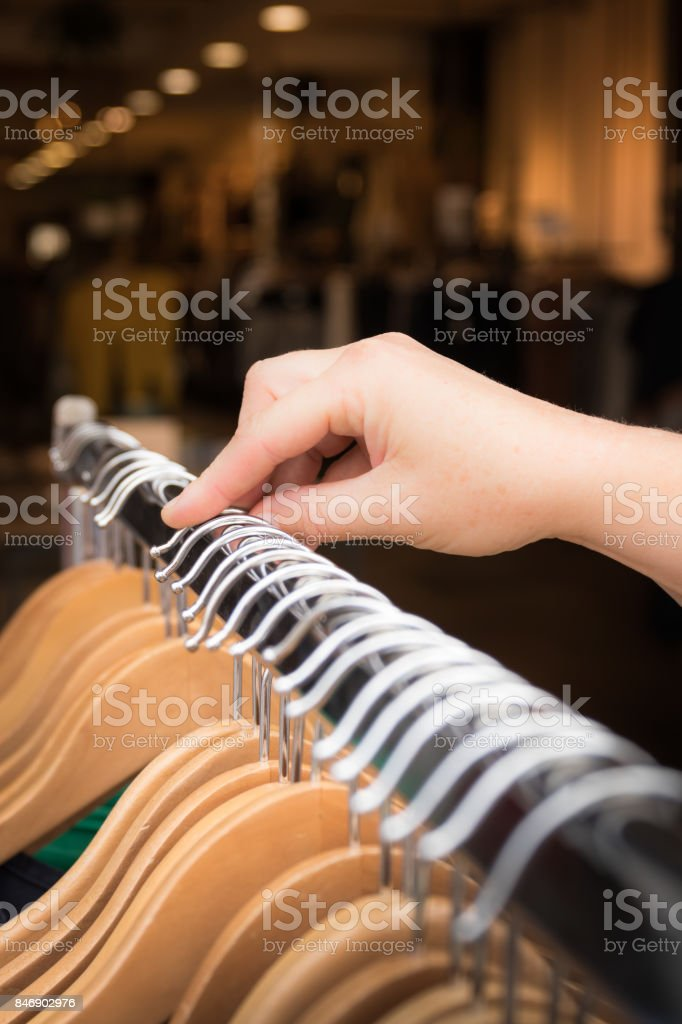Hand of a shopping woman, moving through a row of clothes on a clothes hanger. stock photo