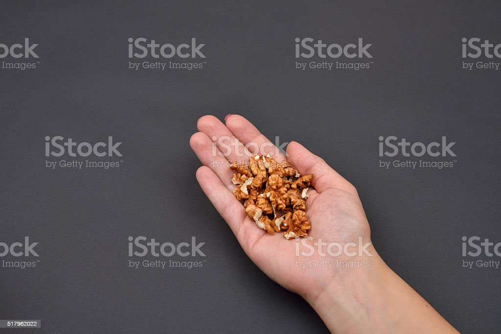 Hand of a woman holding a pile of peeled walnuts stock photo