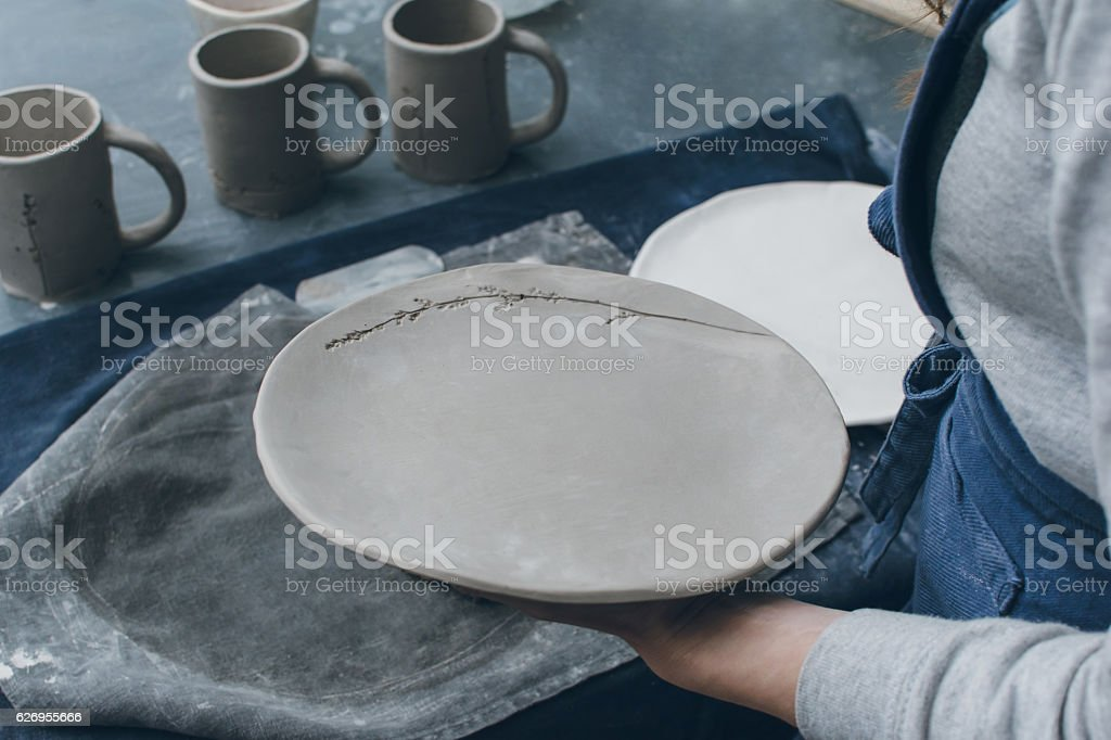 Hand of a woman holding handmade pottery dish stock photo