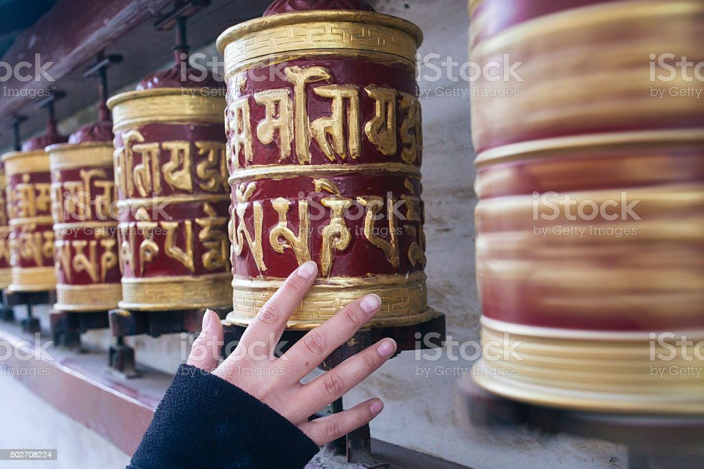 Hand of a woman rotating prayer wheels in a monastery. stock photo