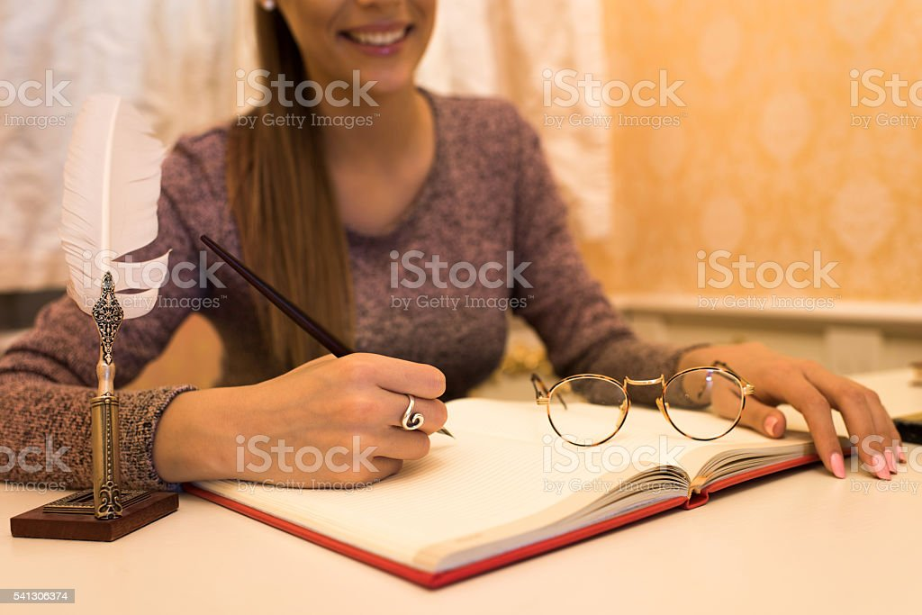 Hand of a woman taking notes with fountain pen. stock photo