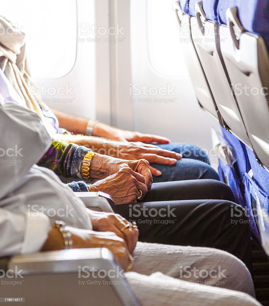 hand of an elderly lady sitting in the aircraft stock photo