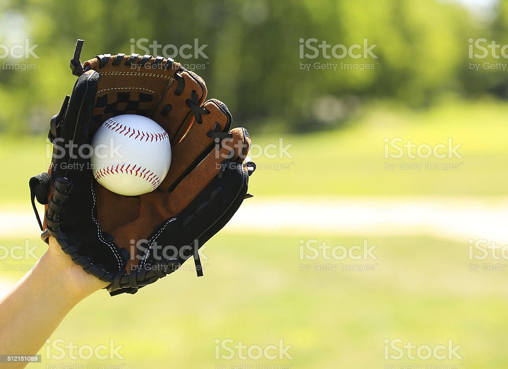 Hand of Baseball Payer with Glove and Ball over Field stock photo