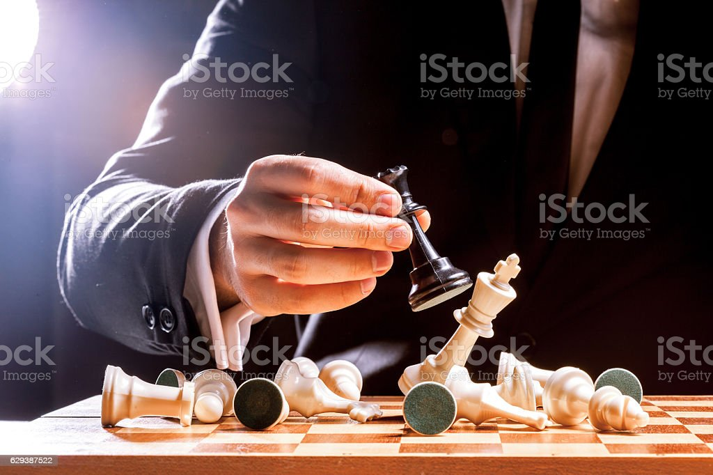 Hand of businessman playing chess stock photo