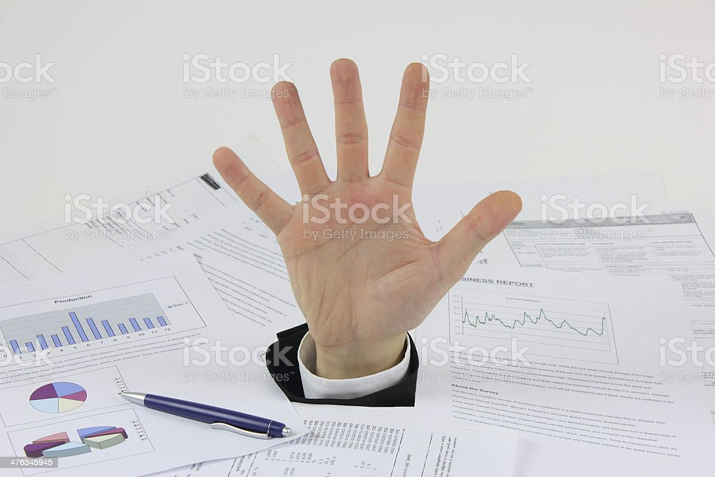 Hand of businessman who drowned in documents royalty-free stock photo