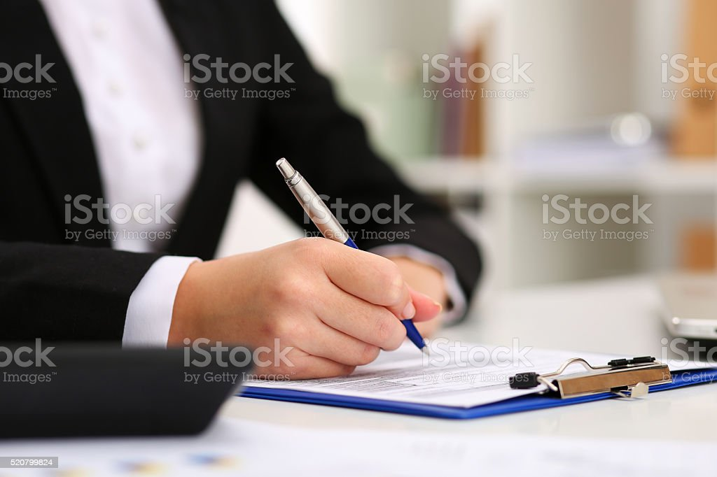 Hand of businesswoman filling and signing with silver pen partne stock photo
