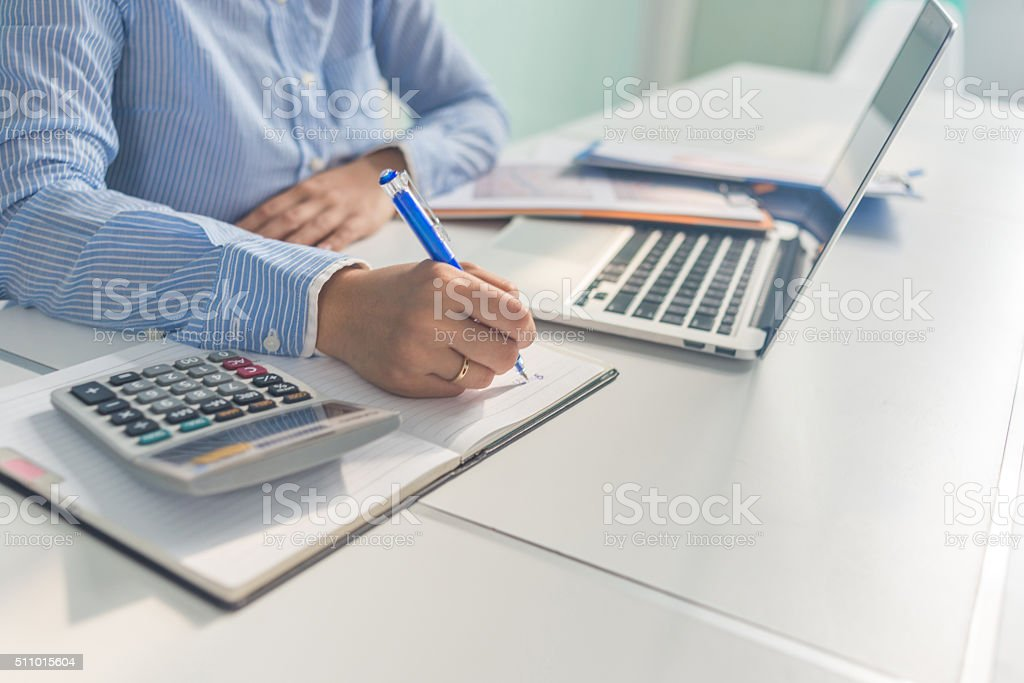 Hand of businesswoman in shirt taking notes from laptop stock photo