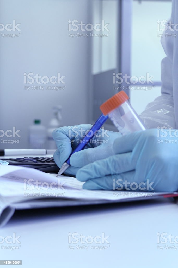 Hand of chemist with pen writing down observations royalty-free stock photo