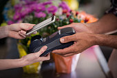 Hand of customer making payment through smartphone