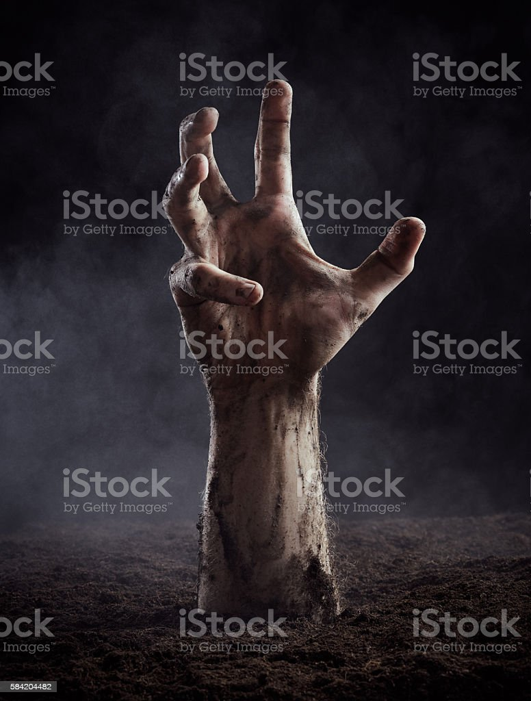 Hand of dead climbs out of the ground stock photo