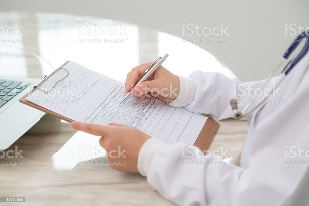 Hand of doctor writing on prescription stock photo