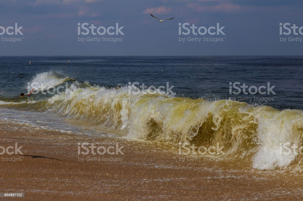 Hand of drowning man trying to swim out of the stormy ocean. stock photo